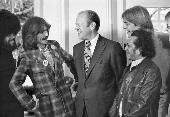 President Gerald Ford smiles as he talks with George Harrison, second from left, at the White House in Washington, Dec. 13, 1974.  Jack Ford, 22, the president's son, second from right, invited Harrison to the White House for lunch.  With them are keyboardist Billy Preston, far left, and sitar player Ravi Shankar, right.