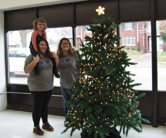 Ja'dn Lindig, Billie Lynne Paynter, and Jessica Paynter, from left, stand by the remembrance tree at Hopewell.