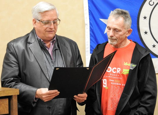 Mayor Steve Mercer presents a proclamation to Hubie Cushman for his serving as an international ambassador for the City of Coshocton by creating the Indian Mud Run and participating in adult obstacle courses all over the world.