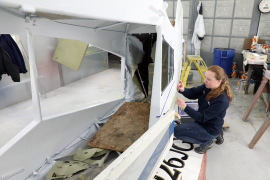 Jenny Haver tapes off a plane for painting at MMS Aviation in Coshocton. Haver is an aircraft maintenance supervisor for the company.