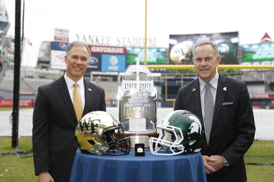 Michigan State coach Mark Dantonio, right, and Wake Forest coach Dave Clawson pose with the Pinstripe Bowl trophy on Tuesday, Dec. 10, 2019, at Yankee Stadium in New York.