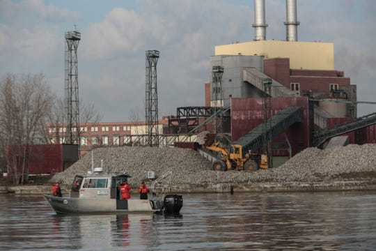 Limestone is moved into piles to be loaded onto barges to build the fourth reef in the Belle Isle Fish Spawning Reef Project in the Detroit River at the now-shuttered DTE Conners Creek coal-fired power plant on Nov. 30, 2016.