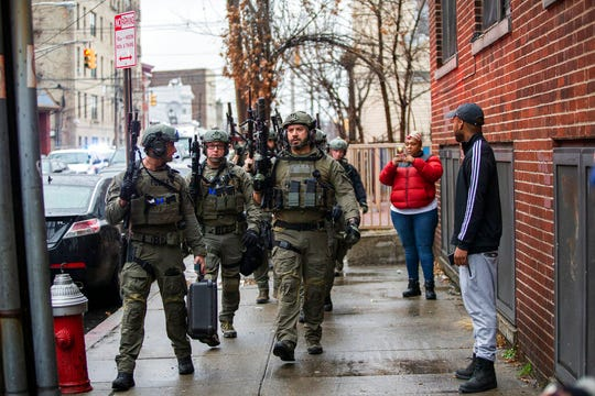 Police officers arrive at the scene following reports of gunfire, Tuesday, Dec. 10, 2019, in Jersey City, N.J.
