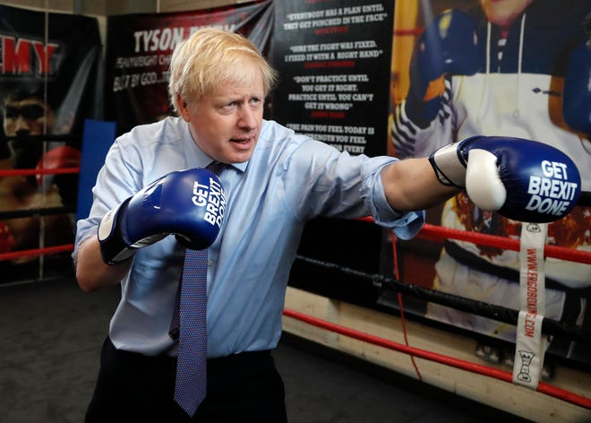 In this Tuesday, Nov. 19, 2019 file photo Britain's Prime Minister Boris Johnson poses for a photo wearing boxing gloves during a stop in his General Election Campaign trail at Jimmy Egan's Boxing Academy in Manchester, England.