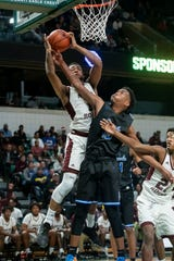 River Rouge forward Brent Darby, left, and Ypsilanti Lincoln guard Deandre Burks battle for a rebound in the first half.