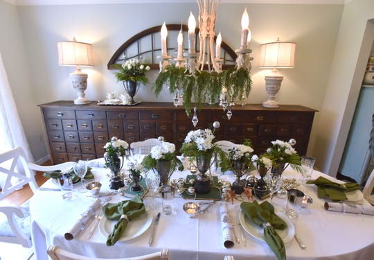 Antique trophies, which Vartoogian collects, serve as vases for flowers for this year's holiday tablescape. The flatware is vintage; one of the sets was a wedding gift to Sandy and her husband, Don.