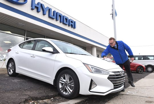 Joe Busch, sales consultant at LaFontaine Hyundai in Dearborn, wipes the ice off of a 2020 Elantra SEL Tuesday. Hyundai saw sales of its compact car increase 102% this November over last year.