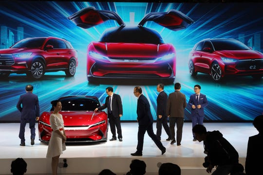 In this April 16, 2019, photo, attendees take a close look at cars from BYD at the Auto Shanghai 2019 show in Shanghai.