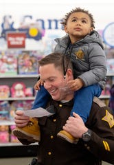 Malakai Freels, 3, hitches a ride on the shoulders of  Vanderburgh County Sheriff Deputy Erik Nilssen during the Christmas with Kids shopping event at Meijer in Evansville Tuesday morning, Dec. 10, 2019.