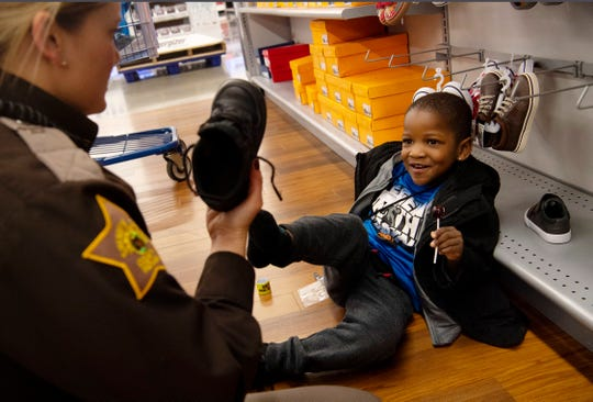 Anthony Smith, 4, is teased by Vanderburgh County Deputy Sheriff Jackie Elder after they picked out new shoes for him during the Christmas with Kids shopping event at Meijer in Evansville Tuesday morning, Dec. 10, 2019. The youngster was adamant his shoe wouldn't fit her.