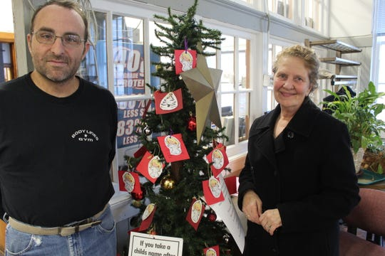 Pontifex Inc. founder Jan Nowak, pictured right and Vaughn Billow stand by the organization's Angel Tree Tuesday. The tree contains tags with a local child's name on them. Residents that wish to donate a Christmas gift to a child listed on one of the tags can do so by Dec. 20.