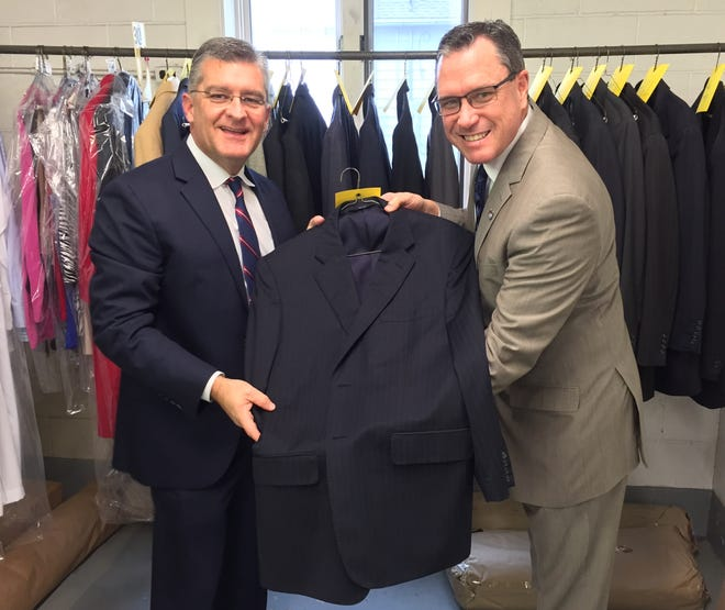"""Nu-Look Cleaners Owner Robby Mills, left, and Brad Schneider show off one of the selections in a suit """"bank"""" that people can borrow from for job interviews, proms, job interviews or other special occasions."""