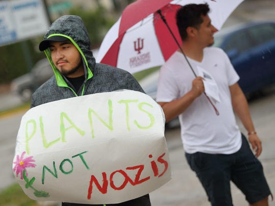 Luis Nieves holds a protest sign June 15 outside the Bloomington Community Farmers' Market.