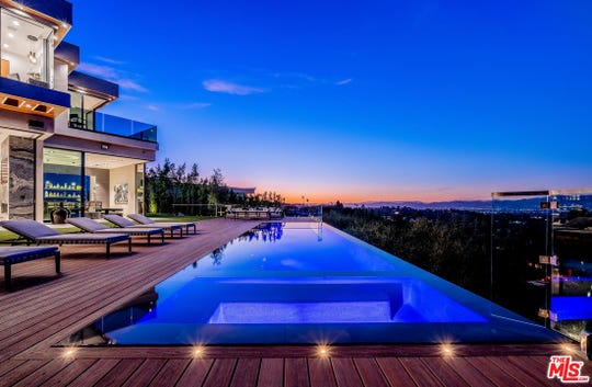 Unobstructed, 180-degree jetliner views of the San Fernando Valley. Outdoor barbecue area, fireplace and a zero edge infinity pool are featured at the Encino home.