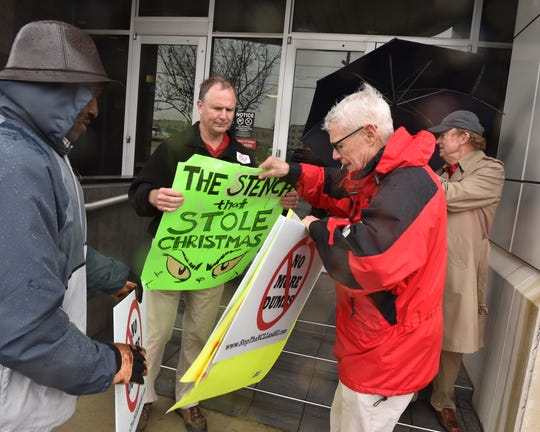 Protesters gather up signs opposing a proposed additional landfill for Madison County before entering a public hearing held by the Mississippi Department of Environmental Quality at its offices in downtown Jackson, Miss., on Tuesday, Dec. 10, 2019.