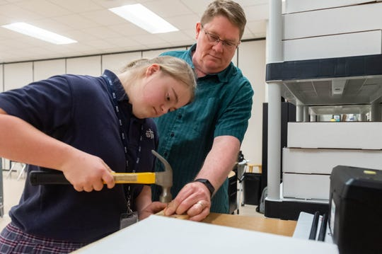Marie Claire Ardoin, a freshman, hammers a nail with teacher Brian Watkins at the Practical Assessment Educational System (PAES) Lab at St. Thomas More Catholic High School. Monday, Dec. 9, 2019.