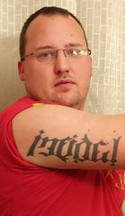 """Ex-Marine Shaun DeWaters, with a tattoo that says """"Infidel,"""" which he says was a term of camaraderie  used by Marines in the Middle East. The state of Kentucky rescinded his """"INFDLS"""" plate on the grounds it was anti-religious."""