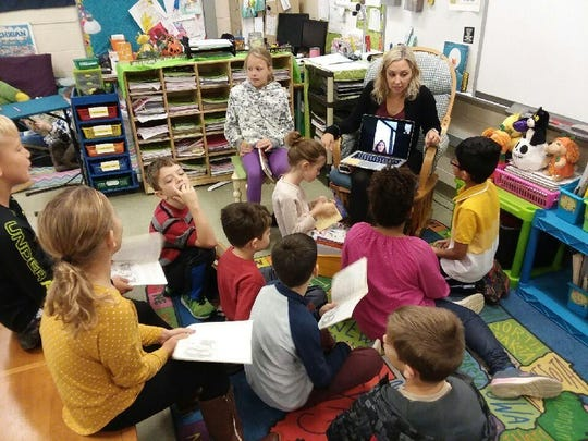 Wilcox Elementary teacher Sarah Kuenner holds a laptop during a classroom lesson, as Charlotte O'Donnell, 8, listens in from her room at Mary Free Bed Rehabilitation Hospital in Grand Rapids this fall. Charlotte often called in to be part of the class during her stay at the hospital.