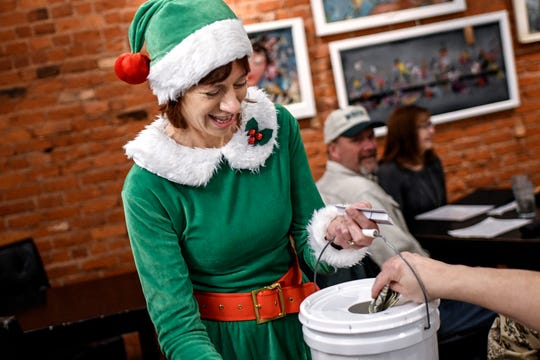 Anne Readett takes donations from a patron at The Bistro as the Knights in Harmony sing for customers on Friday, Dec. 6, 2019, in Williamston. The four-part harmony group, from St. Martha Catholic Church in Okemos, traveled around to Williamston restaurants singing to raise money for food banks.