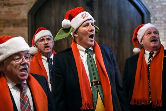 From left, Bill LaRue, Steve Kennedy, David Mackson and Norm Shinkle sing for patrons at Tavern 109 on Friday, Dec. 6, 2019, in Williamston. The Knights in Harmony singing group, from St. Martha Catholic Church in Okemos, traveled around to Williamston restaurants singing to raise money for food banks.