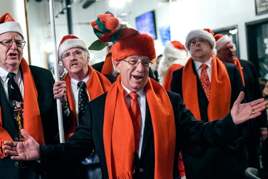 Frank Fortier, center, sings with the Knights in Harmony, a four-part harmony group, for customers at Old Nation Brewery on Friday, Dec. 6, 2019, in Williamston. The group, from St. Martha Catholic Church in Okemos, traveled around to area restaurants singing to raise money for food banks.