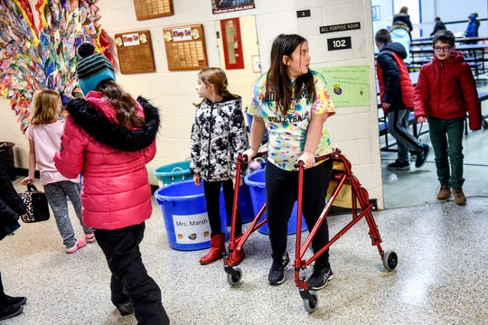 Charlotte O'Donnell, 8, center, uses a walker to get from the cafeteria to the game room where she plays games with friends during recess on Friday, Nov. 22, 2019, at Wilcox Elementary School in Holt.