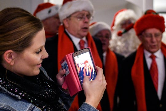 Krysten Lardie takes a video as the Knights in Harmony sing at The Bistro on Friday, Dec. 6, 2019, in Williamston. The group, from St. Martha Catholic Church in Okemos, traveled around to area restaurants singing to raise money for food banks.