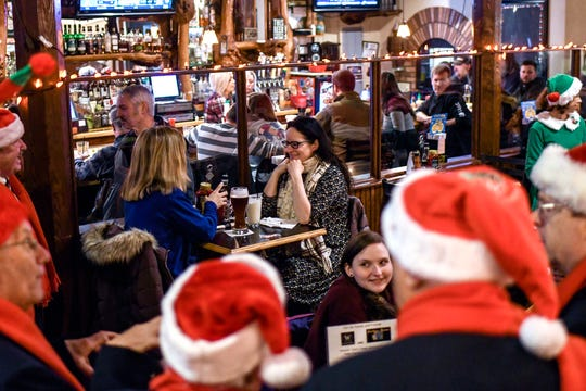 Guests listen as the Knights in Harmony perform at the Williamston Pub & Grill on Friday, Dec. 6, 2019, in Williamston. The group, from St. Martha Catholic Church in Okemos, traveled around to Williamston restaurants singing to raise money for food banks.