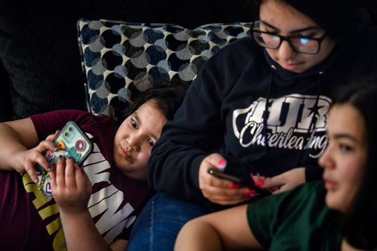 Charlotte O'Donnell, left, 8, plays around with camera filters on a phone while hanging out with family friend Teresa Meeder, center, and sister, Allison O'Donnell, on Tuesday, Nov. 19, 2019, their home in Holt.