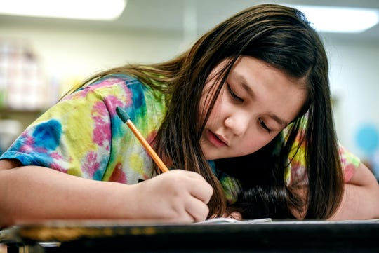 Third-grader Charlotte O'Donnell works on school work in her classroom on Friday, Nov. 22, 2019, at Wilcox Elementary School in Holt.