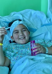 Charlotte O'Donnell, 8, blowing bubbles from her hospital bed. The Wilcox Elementary third grader was severely injured during a crash in June.