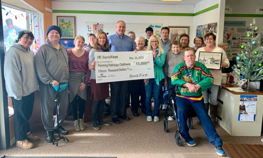 Bank First presents a check for $15,000 to Painting Pathways Clubhouse in downtown Manitowoc.
