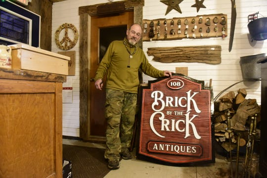 Jeff Wilkinson shows off the new sign for his Lexington shop, Brick by the Crick.