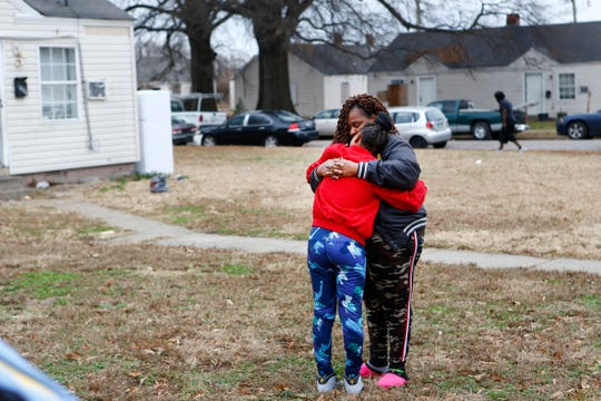 Jacqueline Parson hugs her grandaughter Arieana as they mourn the loss of the girl's mother, Sierra Parson, 31, who was shot and killed late Sunday night in the Evergreen Gardens neighborhood, leaving behind 10 children ages 6-months to 15 years old.