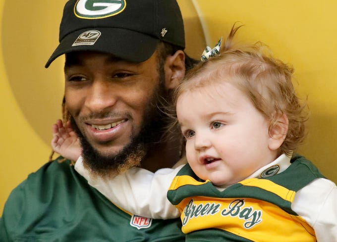 Green Bay Packers running back Aaron Jones sits with 14-month-old Grace Emerald Wensink of Wauwatosa as her grandfather, Pete Fleming (not pictured), of Milwaukee takes a photo at the Hunger Task Force headquarters.