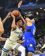Bucks forward Giannis Antetokounmpo tries to get to the basket despite the contact of Orlando Magic forward Aaron Gordon.
