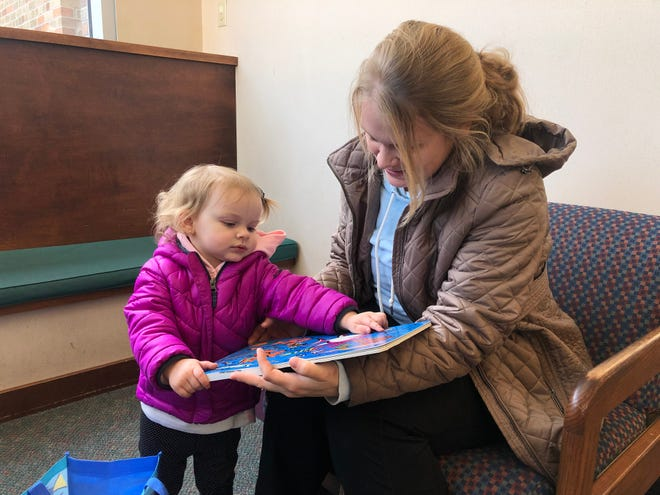 Zoey (left) and Stephanie Duranso read a book at the Wauwatosa Children's Library. They were both happy to hear that the library decided to stop collecting overdue fines on their children's books on Monday, Dec. 9.