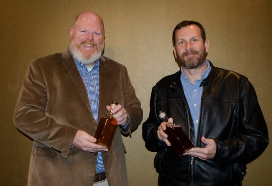 Co-owners of Two Warriors Meadery Cameron Myers, left, and Curtis Sims pose for a photo while holding bottles of mead at the meadery in West Monroe, La. on Dec. 10. The pair plans to open the location to the public for a soft opening this Saturday.