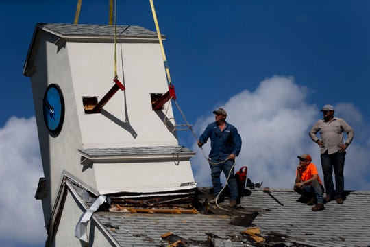 Chad Flint, Yandi Perez, and Austin Flint, of Flint and Doyle Structural Movers, help Kevin Alicea, of K&J Crane Service,  to take down the steeple from the original First Baptist Church before the building is demolished and replaced with condos on 7th Avenue South in Naples on Tuesday, December 10, 2019.