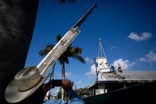 Manny Flint, left, of Flint and Doyle Structural Movers, takes a photo as Chad Flint, Yandi Perez, and Austin Flint help Kevin Alicea, of K&J Crane Service, take down the steeple from the original First Baptist Church before the building is demolished and replaced with condos on 7th Avenue South in Naples on Tuesday, December 10, 2019. The steeple will be donated to St. Matthew's House for part of a new chapel that will be built at the Jill's Place Retreat Center in Alva.