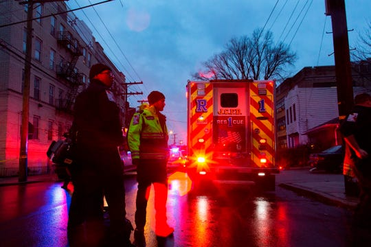 First responders and law enforcement personnel stand near the scene following a shooting, Tuesday, Dec. 10, 2019, in Jersey City, N.J.