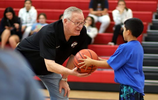 Deming Elks member Don hands the basketball to a Hoop Shoot contestant.