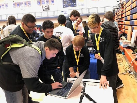 From left to right, Bloomfield High School students Jacob Berryhill, Kyron Keith, Eduardo Arevalo, Cash Snell and Andrew Pearson are seen participating in the New Mexico Governor's STEM Challenge in Albuquerque on Dec. 7, 2019.