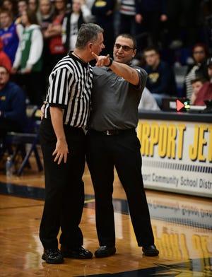 Catholic Central head coach Brandon Sinawi talks to a referee.