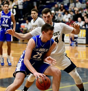 Catholic Central sophomore forward Cooper Craggs is guarded by Airport forward Garrett Gilstorff.