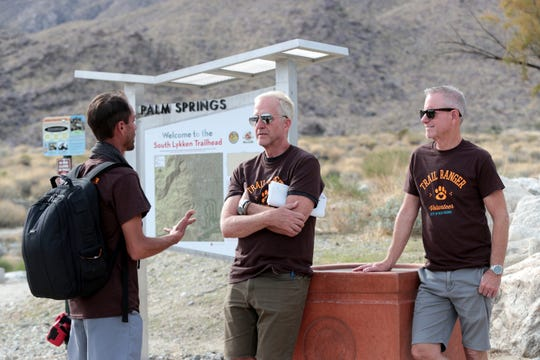 Volunteer trail rangers Scott Collins, left, Jim Flanagan, and Keith Kincaid station themselves at the South Lykken Trailhead in Palm Springs, Calif., on December 10, 2019. They volunteer their time to help protect the bighorn sheep by informing hikers of the prohibition of dogs on some trails in Palm Springs.