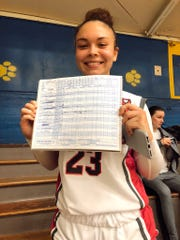Madison Tremblay of Rancho Mirage holds up the score sheet from her record-breaking 57-point game.