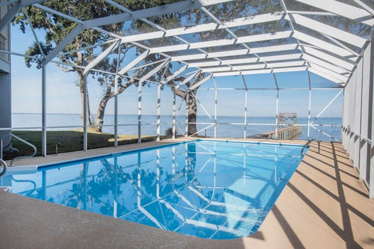 The screen enclosed pool is a refreshing spot to relax and entertain.