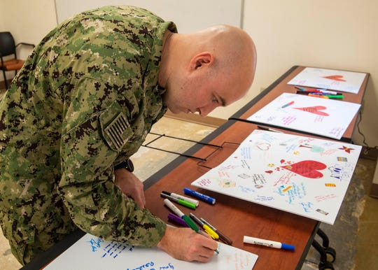 "Airman Apprentice Tyler Smith signs ""get well soon"" cards for those wounded in a deadly attack at NAS Pensacola on Friday, Dec. 6, 2019. The cards will soon be delivered to service members and law enforcement who were injured."