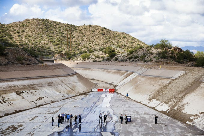 People stand in the emptied Central Arizona Project canal near the Salt Gila Pumping Plant, about 25 miles east of Phoenix. Part of the canal has been emptied for 6 weeks while repairs are being done.